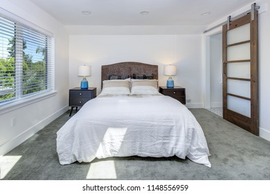 Amazing white bedroom design with king size bed beside a sliding barn door leading to master bathroom.