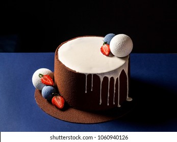 Amazing White Mousse cake covered with chocolate velvet and decorated with chocolate spheres. Whole cake, horizontal photo, dark background, text space above