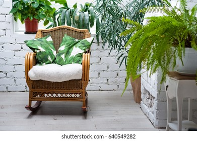 Amazing white room with beautiful green flowers. Wicker chair and a white fireplace. Silence, tranquility, peace in a house in Loft style
