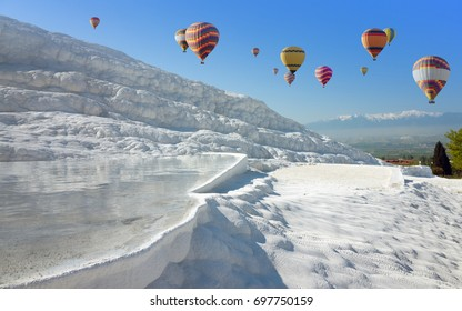 Amazing white travertine terrace formations, pool with clear hot water from thermal springs in Pamukkale, Denizli Province in southwestern Turkey. Hot air ballons flying above white Pamukkale.
