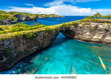 Amazing wild nature view sandy beach with rocky mountains and azure lagoon with clear water of Indian ocean at sunny day / Bali, Indonesia