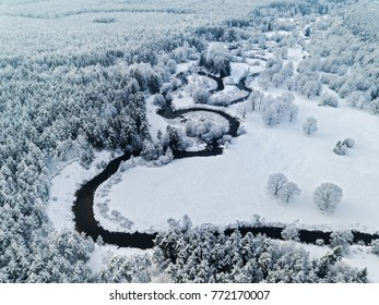 Amazing wild river in blue frozen forest. Really snowly winter on the north. Aerial panoramic view.