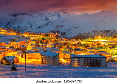 Amazing winter colorful sunset landscape, alpine buildings and spectacular street lights at evening, Alpe d Huez, France, Europe