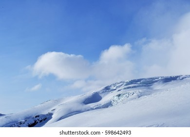 amazing winter mountain landscape. there are snow peaks, ridge, blue sky, floating clouds in photo. beautiful view from ski slope.