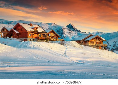Amazing winter sunset landscape and ski resort with spectacular wooden houses in French Alps, Alpe D Huez, France, Europe
