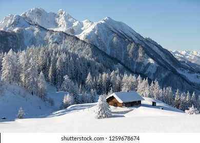 Amazing winter wonderland mountain scenery with traditional alpine hut and snowy mountains at the background