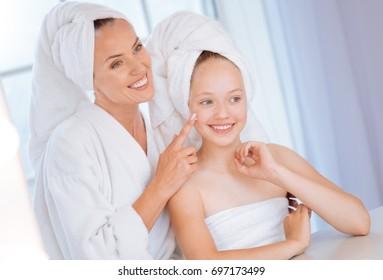 Amazing woman applying cream on cheek of her daughter