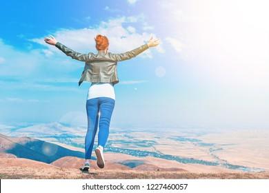 Amazing Woman Outdoors raising hands in sunlight rays. Beautiful Teenage Model girl running on the mountain, Sun Light. Glow Sun. Free Happy Woman. Feel Fly