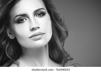 Amazing woman portrait. Beautiful girl with long wavy hair. Blonde model with hairstyle black and white. Studio shot.