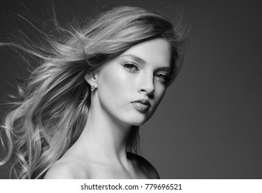 Amazing woman portrait. Beautiful girl with long wavy hair. Blonde model with hairstyle over gray background monochrome black and white