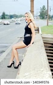 Amazing woman sitting on the roadside, wearing black dress and high heels