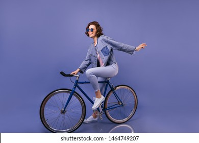 Amazing woman in spring clothes sitting on bicycle. Indoor portrait of lovely girl in sunglasses fooling around on violet background.