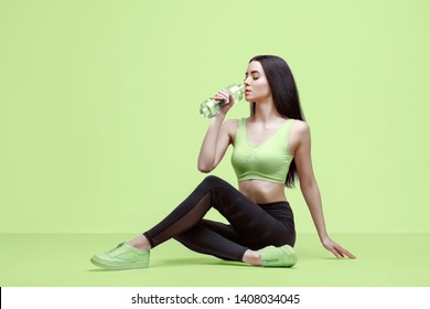 Amazing woman in trendy sportswear drinking water from bottle to stay hydrated after workout. Beautiful slim brunette young girl in fashion leggings and top on green background.