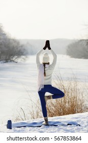 Amazing Yoga girl standing on one leg in the asana with praying hands. Looking at the river.