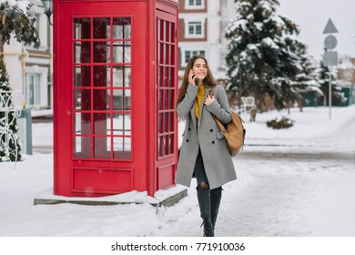 Amazing young woman in gray coat talking on phone on the street with green spruce on background. Outdoor photo of glad busy girl with brown bag walks near red call-box.