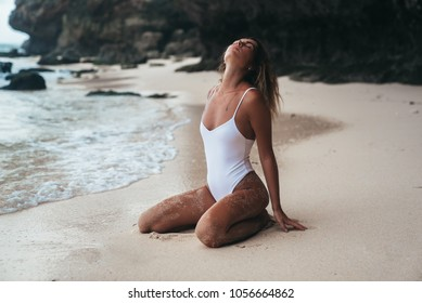 Amazing young woman is resting on the beach. Tanned girl in a white bathing suit. Portrait of a model near a rock