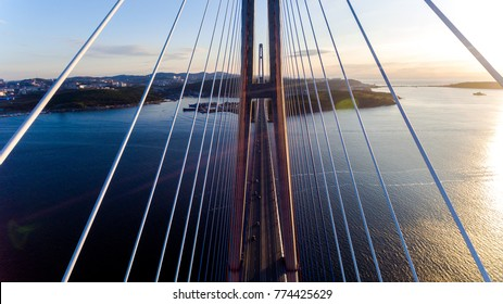 Amazing zooming out aerial view of the Russky Bridge, the world's longest cable-stayed bridge, and the Russky (Russian) Island in Peter the Great Gulf in the Sea of Japan. Sunrise. Vladivostok, Russia