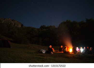 amazingly beautiful landscape with a view of the starry sky in the mountains of Crimea and a group of tourists singing songs by the fire with a guitar