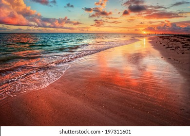 Amazingly colorful sea beach sunset with reflective red sand and bright clouds