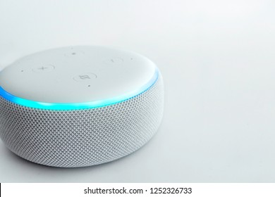 Amazon echo dot, voice controlled speaker with activated voice recognition, on light background.