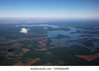The Amazon river and jungle form very high in the air. Aerial view of the blue water river flowing across the tropical rainforest, cropland and plantations.