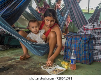 Amazon River, Peru - Sep 12, 2017: People are sitting on  hammock and eating, on a deck of the cargo boat.