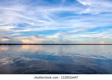 Amazonas, Brazil - River bank in the Amazon rainforest with textured dark waters of Negro river reflecting blue sky and clouds and the forest in the background at dusk.