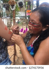 Amazonia Forest, Amazonia, Brazil-february 2018: Indian woman paints the arm of a girl