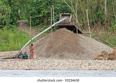 AMAZONIA, PERU - CA NOV 2011 - Local Peruvians participate in illegal gold mining along the Madre de Dios river. This activity has forced the tribes to the riverbank where fatal conflicts arise.