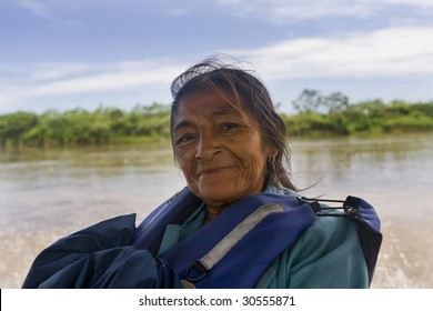 An Amazonian elderly woman riding in a river boat on the Amazon River