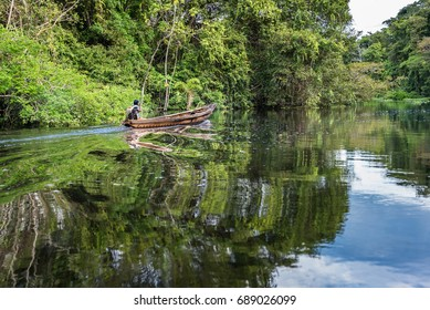 Amazonian man boating in canoe up the Nauta Cano river with small trolling motor