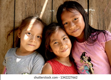 Amazonian Native Group Portrait of Small Girls Smiling in Traditional Wooden Houses of Iquitos Tribes across Rio Negro, Amazon Rainforest. Iquitos, Amazon, Peru, March, 2019