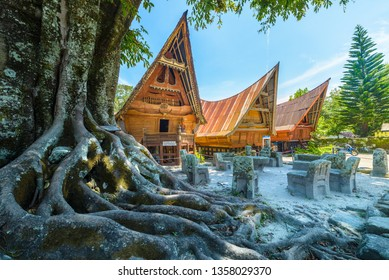 Ambarita, Indonesia - february 22, 2019: Batak traditional houses in a row, tree root in the foreground, teal orange look. Ambarita village, lake Toba, travel destination in Sumatra, Indonesia.