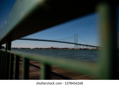 The Ambassador Bridge looking at Detroit from Canada at night fall through a fence