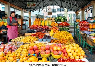 Ambato, Ecuador, December 20, 2017: Ecuadorian woman fruit seller in front of her displays of tropical fruits in a market