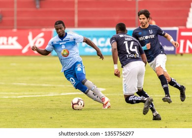 Ambato, Ecuador - March 30. 2019: Match by Liga Pro - Banco Pichincha between the Macará and U. Católica teams. Kéner Arce midfielder Macará takes the ball before the eyes of his opponents.