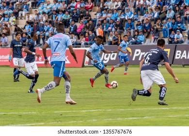Ambato, Ecuador - March 30. 2019: Match by Liga Pro - Banco Pichincha between the Macará and U. Católica teams. Carlos Arboleda rises to the attack surrounded by goal scorers Estrada and Champang.