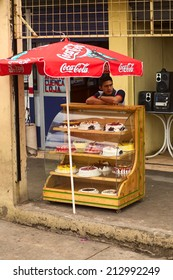AMBATO, ECUADOR - MAY 12, 2014: Unidentified young an standing at a glass case with many different cakes on May 12, 2014 in Ambato, Ecuador.