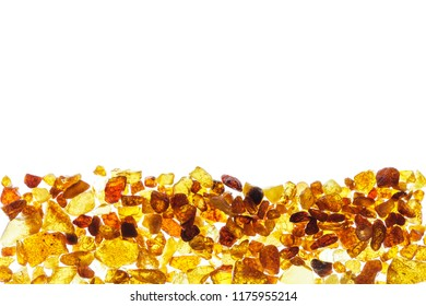 Amber abstract background made of small pieces lying at the bottom