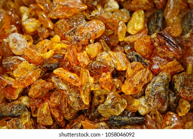 Amber background. A lot of beautiful polished amber stones of different colors. A bunch of natural minerals for jewelers. Raw materials for making ornaments. Red hot amber. Sunstone texture