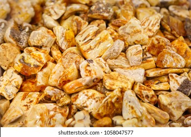 Amber background. A lot of beautiful polished amber stones of different colors. A bunch of natural minerals for jewelers. Raw materials for making ornaments. Large pieces of amber. Sunstone