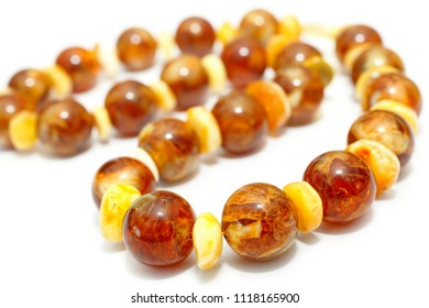 Amber. Beads made from natural yellow brown amber mineral on a white background. Fashionable jewelry amber beads from round and oblong beads. Sun stone as a jeweler raw material. Frozen Resin Fossil