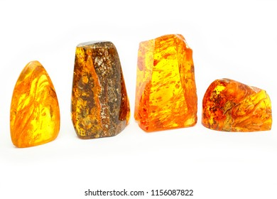 Amber. Beautiful bright transparent pieces of amber of different shapes and colors on a white background. Amber texture and background. Jewelry material from natural mineral fossilized resin. Sunstone