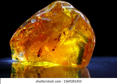 Amber. Beautiful colored transparent piece of amber on a black-blue background. Amber texture. Red-yellow amber with bubbles, waves, divorces and color transitions. Natural mineral Sunstone. Material