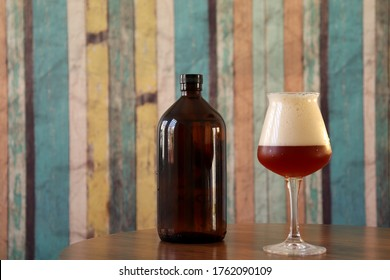 Amber beer in Teku glass with glass growler