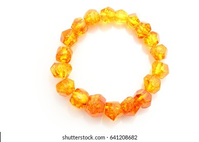 Amber. Amber bracelet decoration on a white background. View of the candle on a bead of sun stone. Semi-precious decoration of yellow color from natural mineral. Top view on the amber decoration.