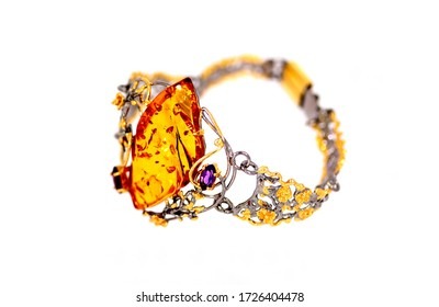 Amber bracelet with a large diamond-shaped amber stone. Small DoF focus put only stone. Transparent honey-colored amber.