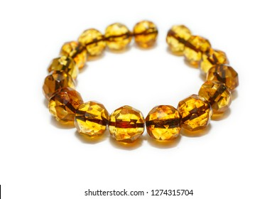Amber bracelet made from round beads with hexagonal amber on a white background. Beads from a natural mineral hardened ancient resin. Jewelry from a sunstone. Jewelry store advertising. Crystals