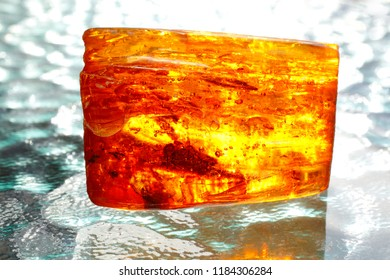 Amber. A bright luminous piece of amber on a background of waves. Fossil resin as a natural material for jewelry. Sunstone. Natural mineral. Crystal. Ancient vintage jewelry. Amber with insect inside