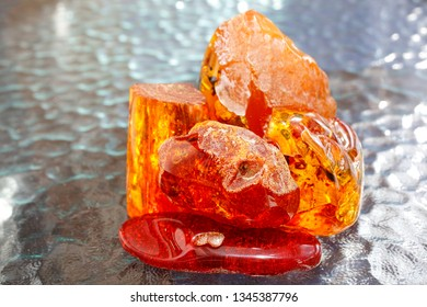 Amber. Bright pieces of amber on the background of blue waves. Amber on a light background. Amber structure as a background. Ancient fossil resin as a mineral. Crystal Material for jeweler. Sun stone